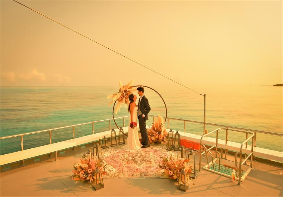 石垣島・八重山諸島アイランド・クルーズ挙式 小浜島竹富島近海・船上サンセット結婚式 アーチ越しに美しい海と夕日を一望する