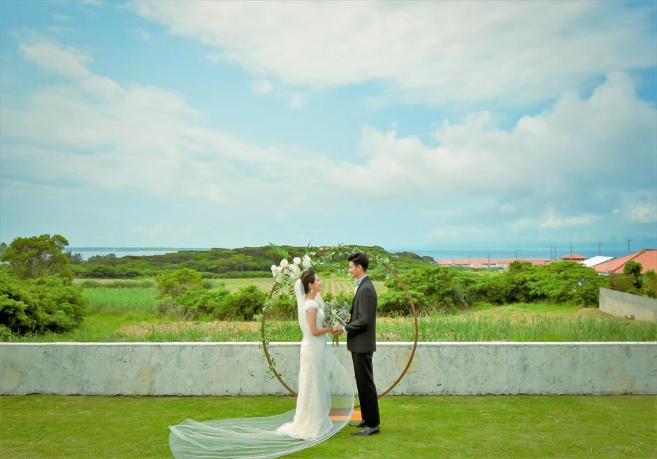 サンセット・ヒル石垣島・沖縄ヴィラ挙式 オーシャンビュー・ガーデン・ウェディング アーチ越しにフサキの美しい景色を一望する