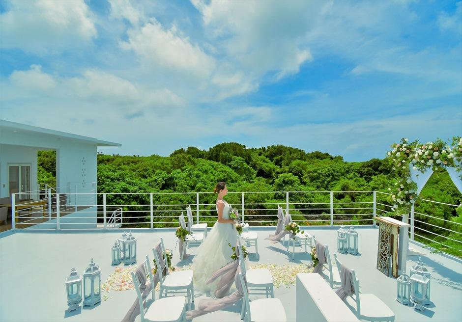 シエスタ・プールヴィラ石垣島・沖縄結婚式 オーシャンフロント・スカイウェディング 緑深い森林とドレス・挙式会場の白が映渡る